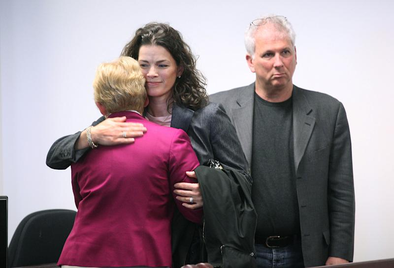 Former Olympic figure skater Nancy Kerrigan, center, hugs her mother Brenda, left, as her husband Jerry Solomon, right, looks on after the first day of testimony in the manslaughter trial of Nancy's brother Mark Kerrigan at Middlesex Superior Court, in Woburn, Mass., Monday, May 16, 2011.  Prosecutors say Nancy's father Daniel Kerrigan died of cardiac dysrhythmia after a violent physical struggle with her brother Mark Kerrigan. (AP Photo/Suzanne Kreiter, Pool)
