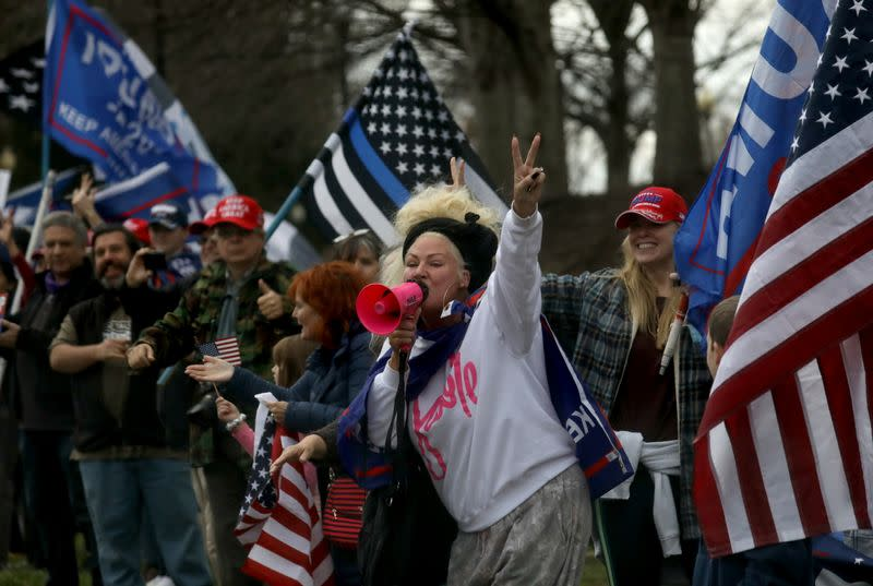 Supporters cheer outside the entrance of Trump National Golf Club as U.S. President Donald Trump's motorcade passes by in Sterling