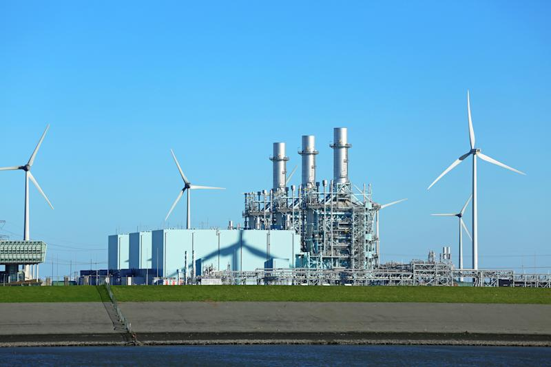A gas-fired power plant alongside some wind-powered turbines.