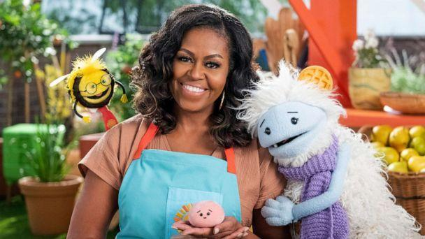 PHOTO: Former first lady Michelle Obama appears with Busy, a bee puppet, left, Mochi, a pink round puppet, and Waffles, a furry puppet with waffle ears on the set of the children's series 'Waffles + Mochi.' (Adam Rose/Netflix via AP)
