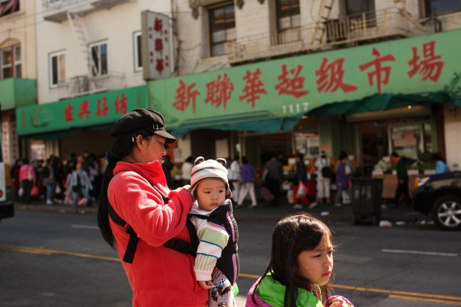 A family waits for a bus in the Chinatown neighborhood in San Francisco, California. With its striking cityscapes and an eclectic offering of food, arts and culture, San Francisco captivates travelers and residents alike.