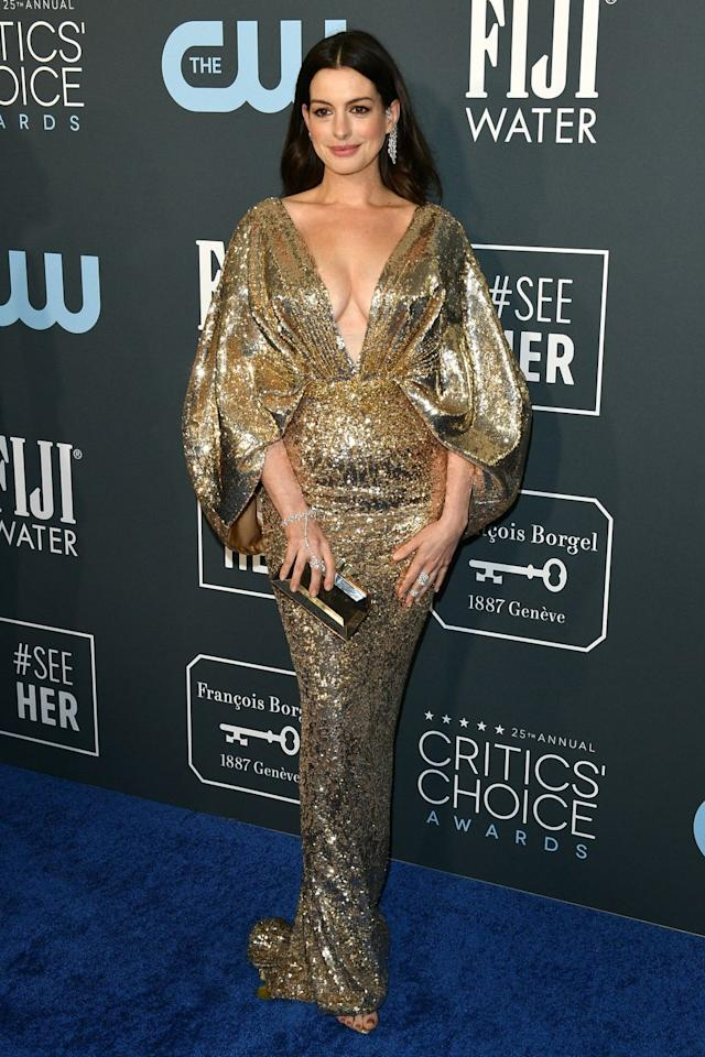 <p>Anne Hathaway sparkles in this gold gown, featuring dramatic puff sleeves and a deep V-cut.</p>