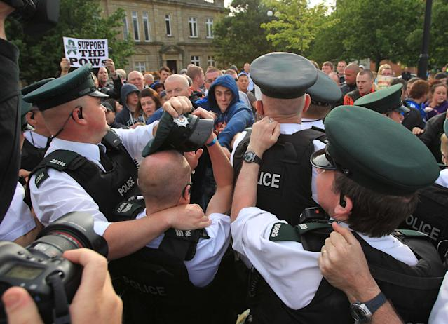 Protestors tussle with police as the Olympic Torch approaches the Peace Bridge in Londonderry , Northern Ireland on June 4, 2012. The torch had to be stopped and re-routed. The Olympic Torch relay started at Land's End, the southwest tip of England, to begin an 8,000-mile (12,875-kilometre) journey around Britain, with a detour through the Irish capital Dublin. It will culminate in the flame being brought to the Olympic Stadium for the opening of the Games on July 27. AFP PHOTO / PETER MUHLYPETER MUHLY/AFP/GettyImages