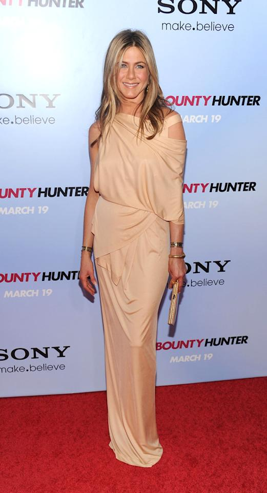 """<a href=""http://movies.yahoo.com/movie/1810129411/info"">The Bounty Hunter</a>"" NY Premiere (2010)    It's any wonder that Gerard Butler could keep his hands off of Aniston as they promoted their movie ""The Bounty Hunter."" This asymmetrical nude Spring 2010 Donna Karan gown is sensual and subtly sexy, and the color perfectly accentuates her glowing skin."