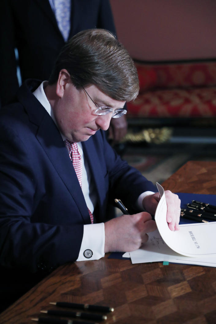 Mississippi Republican Gov. Tate Reeves signs the bill retiring the last state flag in the United States with the Confederate battle emblem, at the Governor's Mansion in Jackson, Miss., Tuesday, June 30, 2020. The signature removes official status for the banner that has been a source of division for generations. (AP Photo/Rogelio V. Solis, Pool)