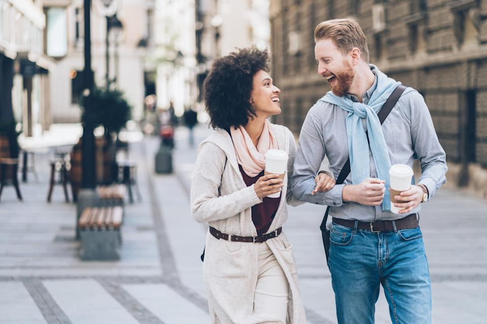 Happy young couple walking on the street drinking coffee and laughing