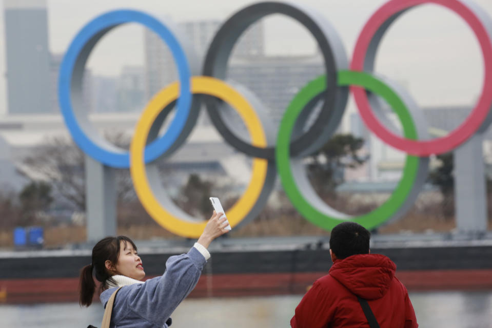 A woman poses for a selfie in front of Olympic rings at Odaiba waterfront in Tokyo, Tuesday, Jan. 26, 2021. The postponed Tokyo Games are scheduled to open on July 23. (AP Photo/Koji Sasahara)