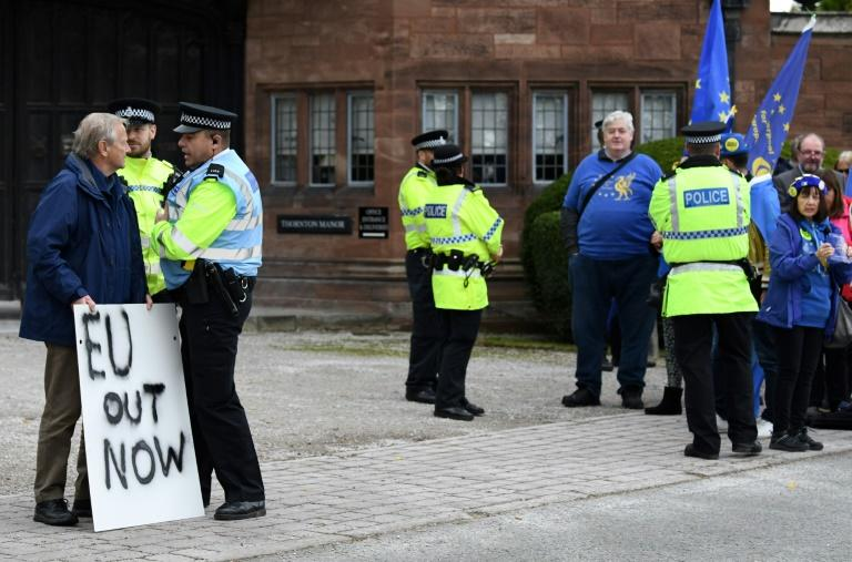 A pro-Brexit demonstrator (L) and a group of anti-Brexit protestors gathered outside the meeting at Thornton Manor