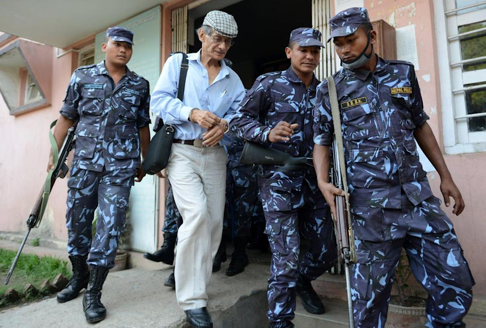 French serial killer Charles Sobhraj (2nd L) is escorted by Nepalese police to a waiting vehicle after a hearing at a district court on a case related to the murder of Canadian backpacker Laurent Ormond Carriere, in Bhaktapur on June 12, 2014. Sobhraj, a French citizen who is serving a life sentence in Nepal for the murder of an American backbacker in 1975, has been linked with a string of killings across Asia in the 1970s, earning the nickname
