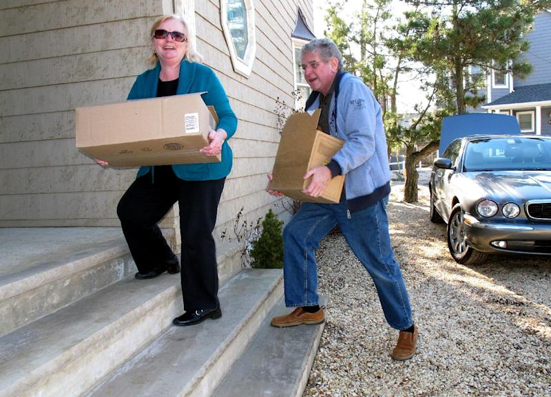 Joanne Murphy, left, and her husband Jim, right, carry boxes of their belongings back into their house in Toms River, N.J. on Monday, Jan. 7, 2013, the first day that some of the hardest-hit parts of the Jersey shore allowed residents to move back home since Superstorm Sandy hit nine weeks ago. Monday was the first day authorities let residents move back home permanently in Seaside Heights and parts of Toms River and Brick. (AP Photo/Wayne Parry)
