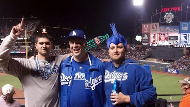 This photo taken on Wednesday, Sept. 25, 2013, and provided by Matthew Gomes, shows, from left to right, Jonathan Denver, his father Robert Preece and his brother Rob Preece at a baseball game between the San Francisco Giants and the Los Angeles Dodgers in San Francisco. Police say Denver was with his father, older brother and two other people a few blocks from the Giants' stadium after leaving the ballpark in the eighth inning of the Giants 6-4 victory when their group exchanged words with some Giants fans. Denver was stabbed to death during the altercation. (AP Photo/Matthew Gomes)