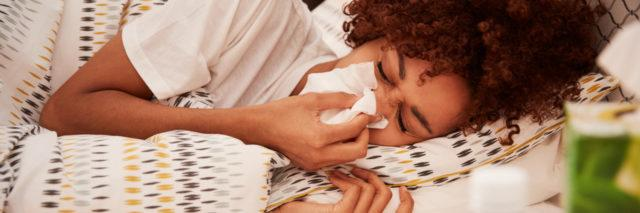 Image of a young African American woman lying in bed blowing her nose into a tissue, side view, close up