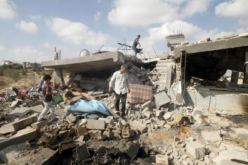 Palestinians salvage their belongings from their destroyed home in Rafah, in the southern Gaza Strip, on August 5, 2014