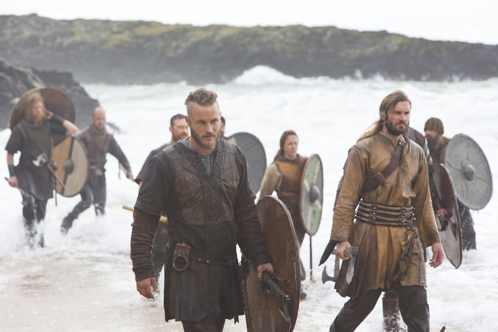 Ragnar (Travis Fimmel), shield in hand with his crew, including Brother Rollo (Clive Standen) after landing ashore in the west