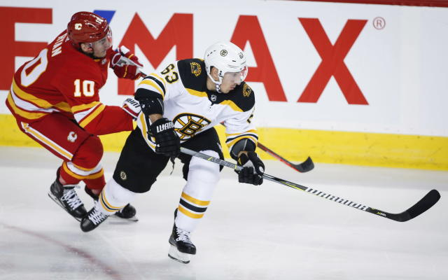 Boston Bruins' Brad Marchand, right, Calgary Flames' Derek Ryan chase the puck during NHL hockey action in Calgary, Alberta, Wednesday, Oct. 17, 2018. (Jeff McIntosh/The Canadian Press via AP)