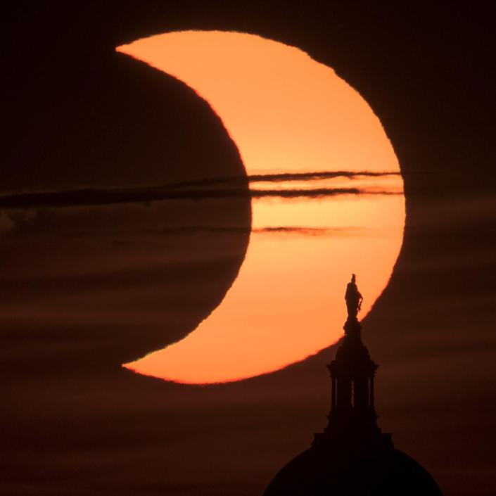 A partial solar eclipse is seen as the sun rises behind the Capitol Building in Arlington, Va.