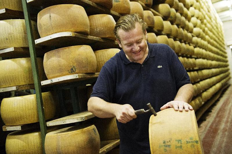 """This book cover image released by Ballantine Books shows Michael White with a wheel of cheese to be used for a dish from his book """"Classico E Moderno: Essential Italian Cooking,"""" with Andrew Friedman. White is the chef and owner of Marea restaurant in New York. (AP Photo/Ballantine Books, Evan Sung)"""