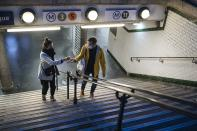 A couple wearing a protective masks leaves the Republique subway station in Paris, Thursday, Oct. 29, 2020. France prepared to shut down again for a month to try to put the brakes on the fast-moving coronavirus. Schools are allowed to remain open in this new lockdown, which is gentler than what France saw in the spring. But still a shock to restaurants and other businesses ordered to close their doors in one of the world's biggest economies. (AP Photo/Lewis Joly)