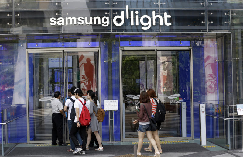 Visitors enter a showroom of Samsung Electronics' at its headquarters in Seoul, South Korea, Friday, July 26, 2013. Samsung Electronics reported a record-high profit for a sixth straight quarter but still disappointed investors who had higher expectations for the world's largest smartphone maker. (AP Photo/Lee Jin-man)