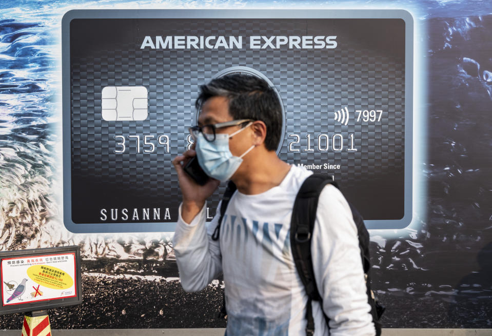 HONG KONG, CHINA - 2021/03/15: A pedestrian wearing a face mask walks past a commercial advertisement billboard of the American multinational financial services corporation and credit card business American Express in Hong Kong. (Photo by Budrul Chukrut/SOPA Images/LightRocket via Getty Images)