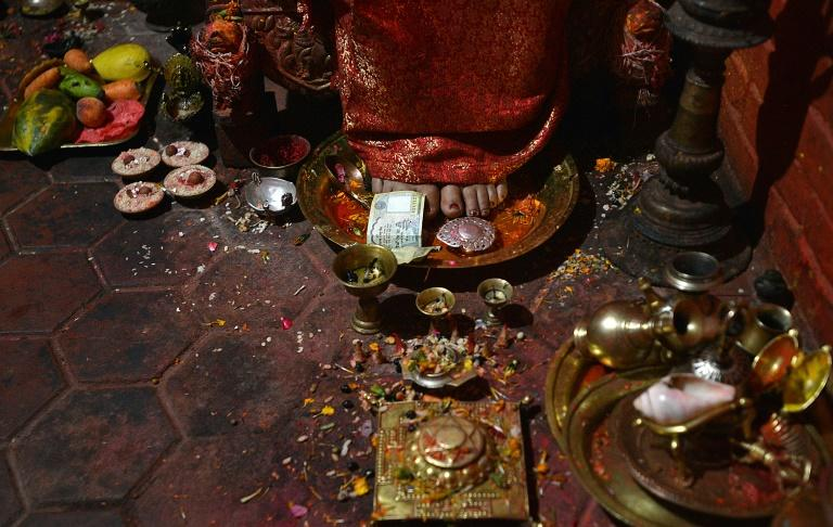 """TO GO WITH: Nepal-quake-religion-goddess, INTERVIEW by Paavan Mathema In this photograph taken on May 21, 2015, Dhana Kumari Bajracharya, the longest reigning Kumari of Nepal, sits in her quarters in Kathmandu. When a massive earthquake struck Nepal in April, the country's longest-reigning """"living goddess"""", Dhana Kumari Bajracharya, left her quarters for the first time in three decades as tremors reduced nearby temples to rubble. AFP PHOTO / Ishara S. KODIKARA"""
