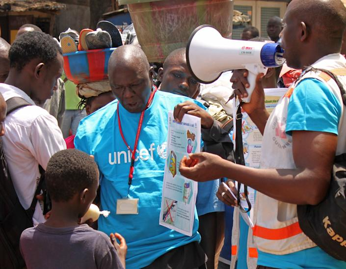"""Health workers teach people about the Ebola virus and how to prevent infection, in Conakry, Guinea, Monday, March 31, 2014. Health authorities in Guinea are facing an """"unprecedented epidemic"""" of Ebola, the international aid group Doctors Without Borders warned Monday as the death toll from the disease that causes severe bleeding reached 78. The outbreak of Ebola in Guinea poses challenges never seen in previous outbreaks that involved """"more remote locations as opposed to urban areas,"""" said Doctors Without Borders. (AP Photo/ Youssouf Bah)"""