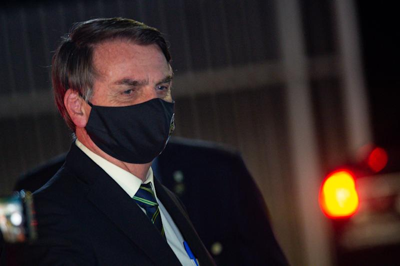BRASILIA, BRAZIL - MAY 27: President of Brazil Jair Bolsonaro, wearing a face mask with a print of Brazil's Coat of Arms and written God above all, Brazil above all, reacts to supporters of his government who waited for him outside the Palácio do Alvorada amidst the coronavirus (COVID-19) pandemic on May 27, 2020 in Brasilia. Brazil has over 411,000 confirmed positive cases of Coronavirus and 25,598 deaths. (Photo by Andressa Anholete/Getty Images)