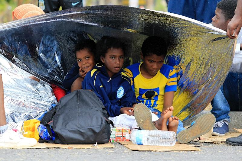 Migrant children shelter as they wait along the road at the Italy-France border, in Vintimiglia, on June, 13, 2015 (AFP Photo/Jean-Christophe Magnenet)