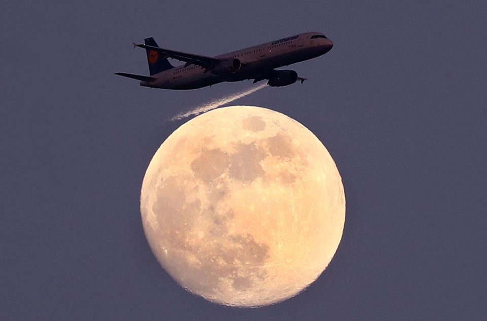 An airplane of German air carrier Lufthansa passes the moon over Frankfurt, Germany, April 9, 2017.  REUTERS/Kai Pfaffenbach      TPX IMAGES OF THE DAY