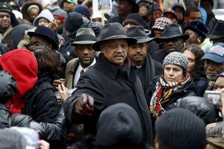 Rev. Jesse Jackson (C) joins demonstrators during a protest intending to disrupt Black Friday shopping in reaction to the fatal shooting of Laquan McDonald in Chicago, Illinois, November 27, 2015. REUTERS/Andrew Nelles