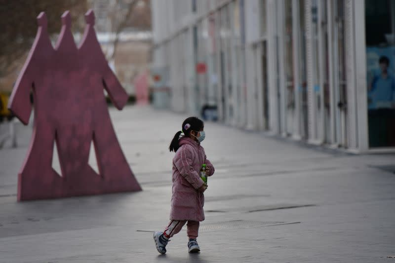 A child wears a face mask in Beijing's central business district