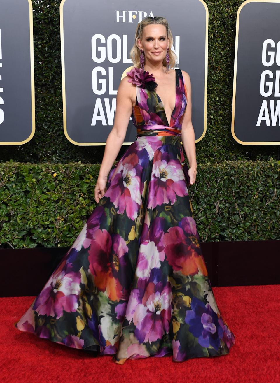 <p>Wearing a floral plunging gown.</p>
