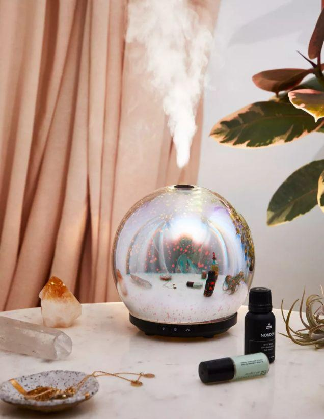 """This diffuser has up to 12 hours of vapor and more than 14 color options with different lighting effects. It has a 4.7-star rating and more than 63 reviews. <a href=""""3D LED Gala Essential Oil Diffuser"""" target=""""_blank"""" rel=""""noopener noreferrer"""">Find it for $65 at Urban Outfitters</a>."""