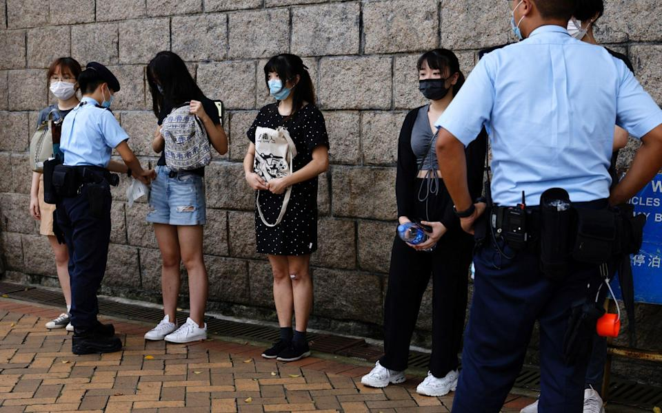 Police stop and search young people outside the High Court. - TYRONE SIU /REUTERS