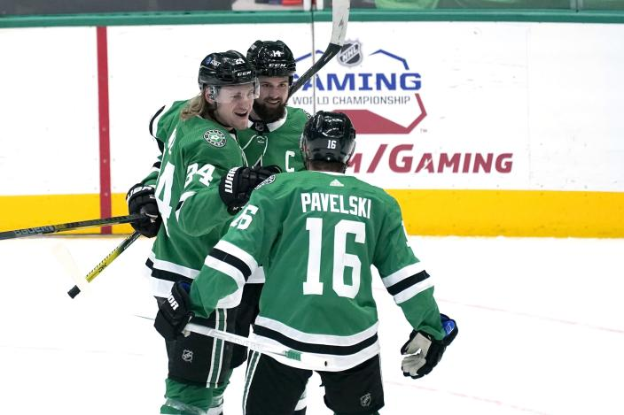 Dallas Stars' Joe Pavelski (16), Roope Hintz (24) and Jamie Benn, rear, celebrate a goal scored by Benn in the first period of an NHL hockey game against the Florida Panthers in Dallas, Saturday, April 10, 2021. Pavelski was credited with the assist on the goal. (AP Photo/Tony Gutierrez)