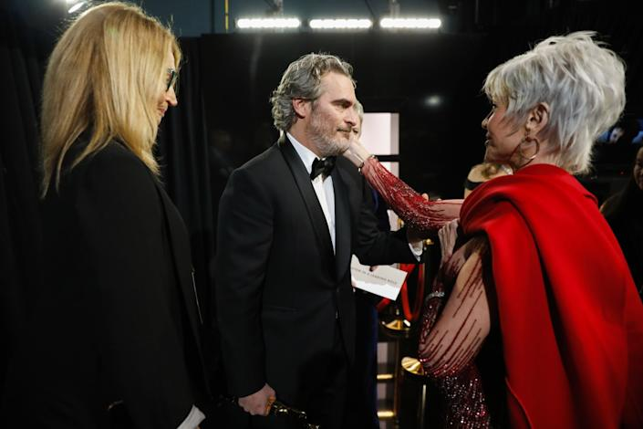 "Joaquin Phoenix, winner of the lead actor Oscar for ""Joker,"" congratulated by Jane Fonda backstage at the Academy Awards in February."