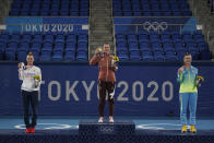 Gold medalist Belinda Bencic, middle, of Switzerland, silver medalist Marketa Vondrousova, left, of the Czech Republic, and bronze medalist Elina Svitolina, of the Ukraine, pose following the women's single matches of the tennis competition at the 2020 Summer Olympics, Sunday, Aug. 1, 2021, in Tokyo, Japan. (AP Photo/Seth Wenig)