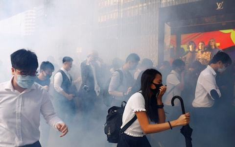 Office workers react after police fired tear gas, in Central, Hong Kong - Credit: REUTERS/Thomas Peter
