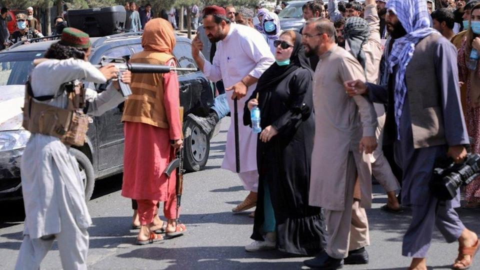 A Taliban fighter points a gun at a woman during a demonstration in Kabul
