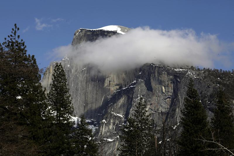 Yosemite Half Dome dusted with snow and clouds in Yosemite National Park is closed to visitors due to the coronavirus