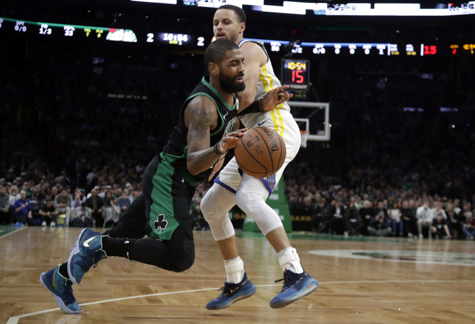 Boston Celtics guard Kyrie Irving, bottom, drives against Golden State Warriors guard Stephen Curry, top, in the first quarter of an NBA basketball game, Saturday, Jan. 26, 2019, in Boston. (AP Photo/Elise Amendola)