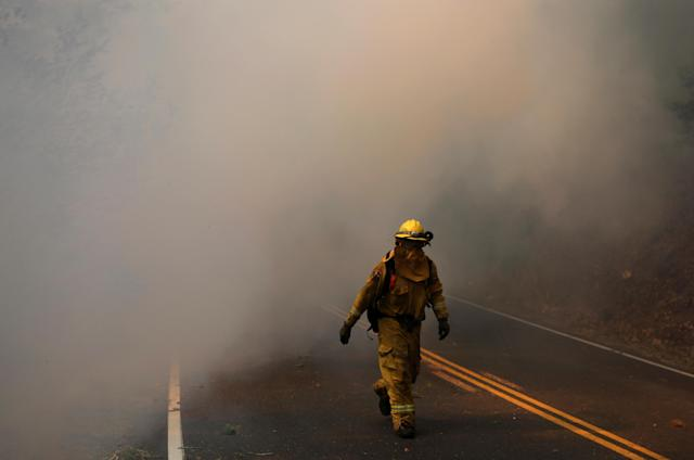 <p>Firefighters work to contain the Tubbs wildfire outside Calistoga, Calif., Oct. 12, 2017. (Photo: Jim Urquhart/Reuters) </p>