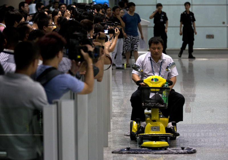 A man drives a cleaning machine near an area where a man set off a homemade bomb at Terminal 3 of the Beijing International Airport in Beijing, China, Saturday, July 20, 2013. (AP Photo/Alexander F. Yuan)