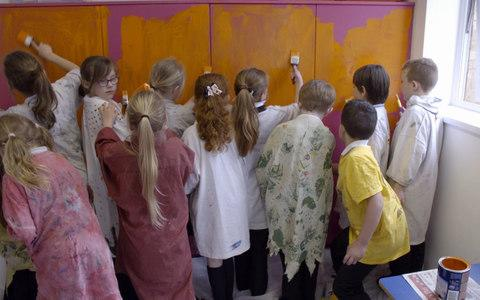 The class get to work painting their classroom