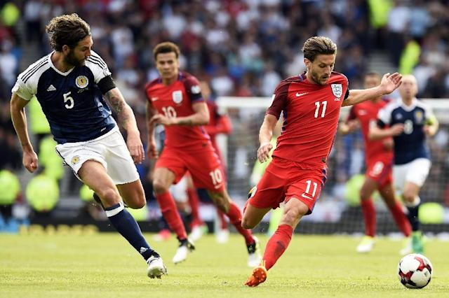 England's midfielder Adam Lallana (R) vies with Scotland's defender Charlie Mulgrew (L) during the group F World Cup qualifying football match in Glasgow on June 10, 2017 (AFP Photo/ANDY BUCHANAN)