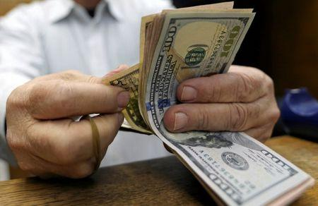 A man counts U.S dollars at a money exchange office in central Cairo