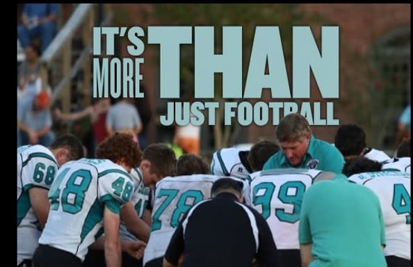 High school football coach Ronnie Mitchem (pictured in front of No. 99) was at the center of a national conversation over protest and the national anthem. (Screengrab via Victory & Praise Christian Academy)