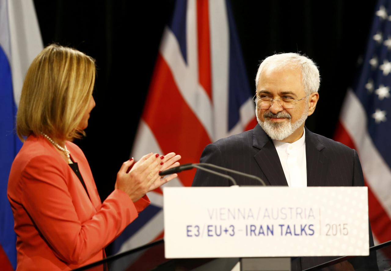 "High Representative of the European Union for Foreign Affairs and Security Policy Federica Mogherini (L) applauds Iranian Foreign Minister Mohammad Javad Zarif during a joint news conference after a plenary session at the United Nations building in Vienna, Austria July 14, 2015. Iran and six major world powers reached a nuclear deal on Tuesday, capping more than a decade of on-off negotiations with an agreement that could potentially transform the Middle East, and which Israel called an ""historic surrender"". REUTERS/Leonhard Foeger"