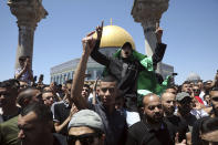A Muslim worshipper wears a Hamas flag during a protest against Israeli airstrikes on the Gaza Strip following Friday prayers at the Dome of the Rock Mosque in the Al-Aqsa Mosque compound in the Old City of Jerusalem, Friday, May 14, 2021. (AP Photo/Mahmoud Illean)