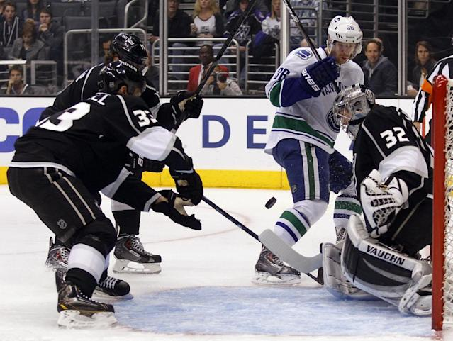 Los Angeles Kings goalie Jonathan Quick (32) stops a shot by Vancouver Canucks right wing Jannik Hansen (36), of Denmark ,with Kings center Anze Kopitar (11), of Slovenia, and defenseman Willie Mitchell (33) defending during the first period of an NHL hockey game on Saturday, Jan. 4, 2014, in Los Angeles. (AP Photo/Alex Gallardo)